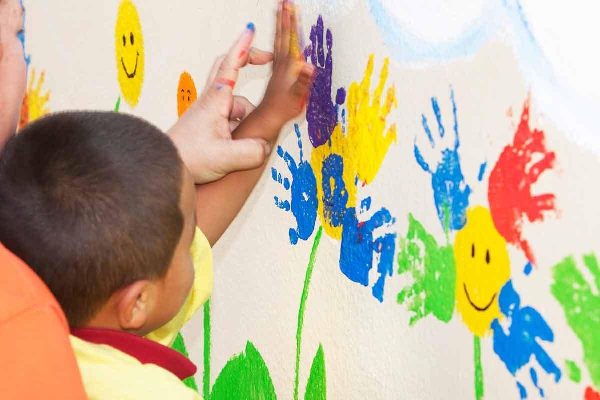 Criança pintando muro||