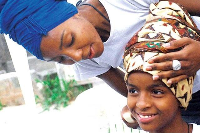 Menina sorri com turbante na cabeça