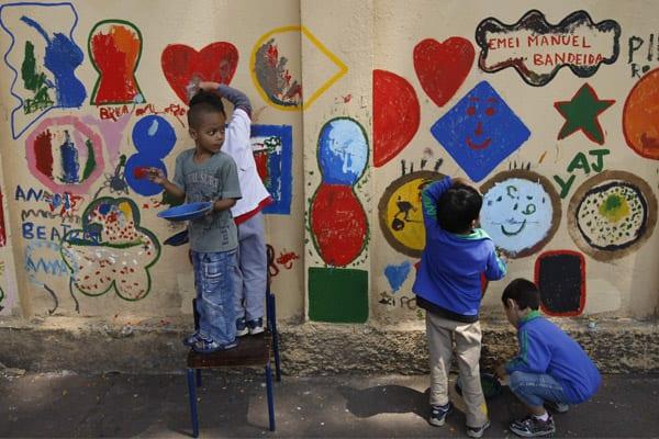 Crianças pintam muro de escola em São Paulo