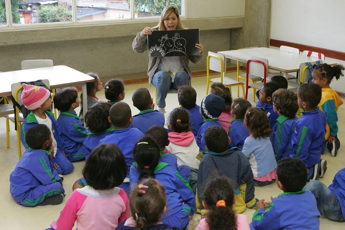 Professora lê com crianças na pré-escola