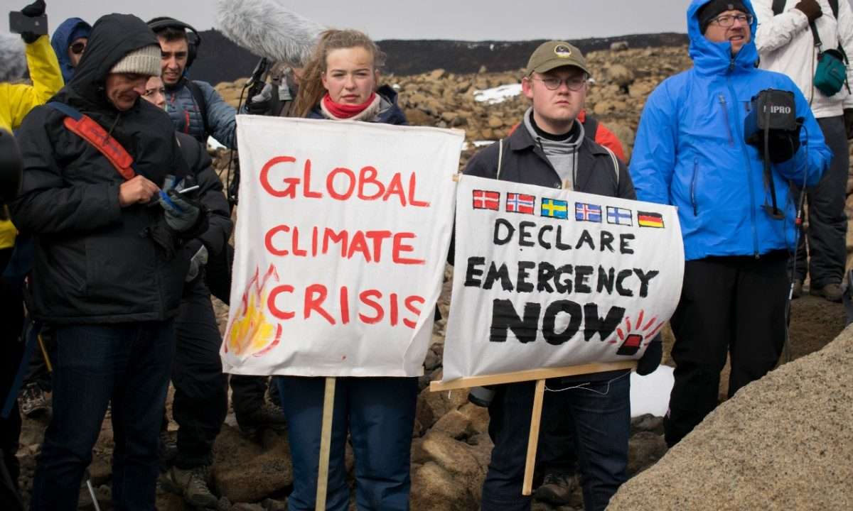 Jovens com placas alertando para a crise climática no planeta (Foto: Jeremie Richard/AFP)