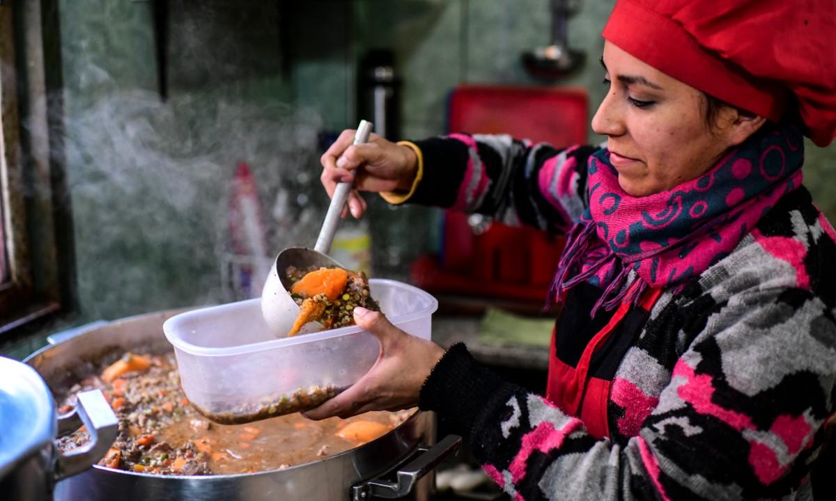 A pobreza na Argentina já afeta 35,4% da população. No foto, uma voluntária serve comida nos arredores de Buenos Aires (Foto: Ronaldo SCHEMIDT / AFP)