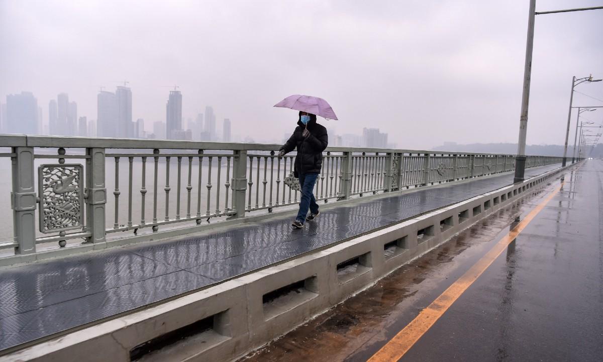 Cidadão de Wuhan caminha em rua vazia - Foto: HECTOR RETAMAL/AFP