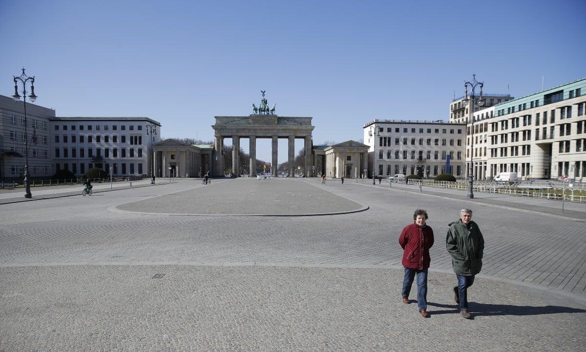 Casal é visto caminhando próximo ao Portão de Brandemburgo, em Berlim (foto: Odd ANDERSEN / AFP)