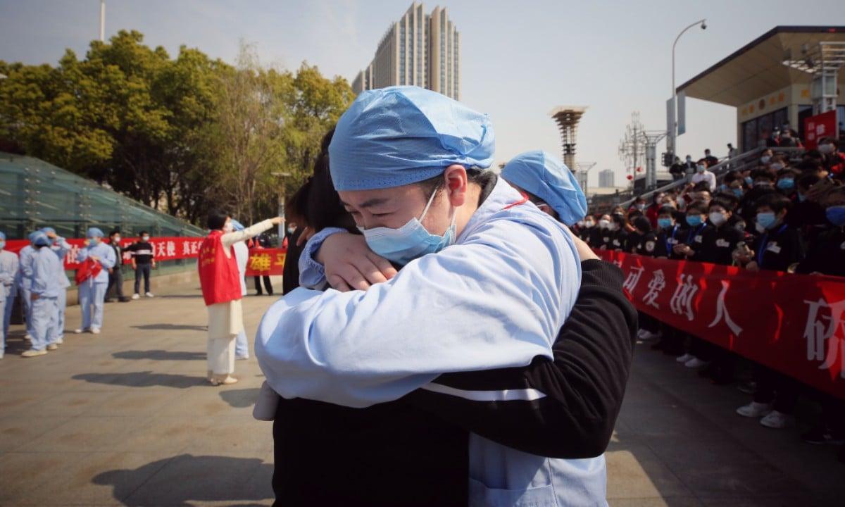 Médico abraça colega na cerimônia de homenagem aos reforços de saúde enviados a Wuhan, China. (Foto: STR / AFP)