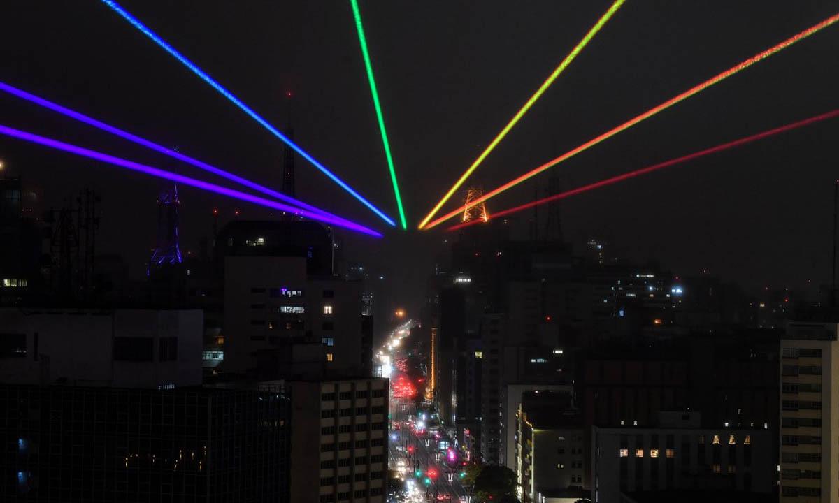 O arco íris visto à longa distância foi projetado na noite paulistana no último dia 14, data da Parada LGBTQI+, cancelada devido ao Covid 19. O arco íris foi obra artística de Yvette Mattern. Foto: Nelson Almeida/AFP