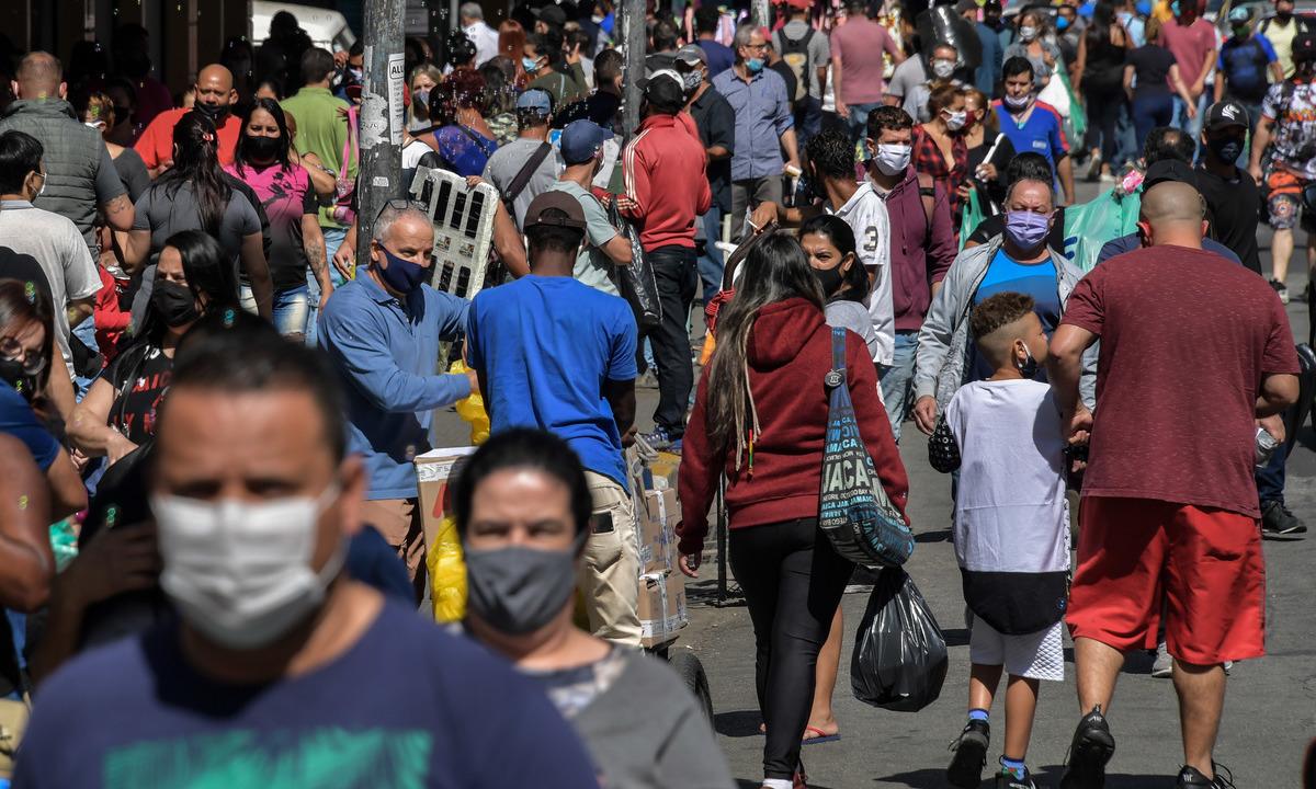 Pessoas caminham em rua comercial de São Paulo. Foto: NELSON ALMEIDA/AFP