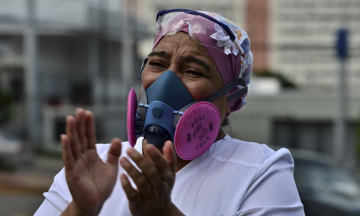 Enfermeira em Honduras chora durante funeral de seu colega, morto por Covid-19. (Foto: Fernando Sierra)