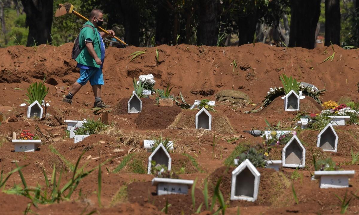Coveiro anda entre covas de vítimas do coronavírus (Foto: Nelson Almeida/AFP)