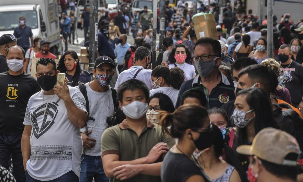 Pessoas caminham nas ruas de São Paulo após reabertura. Foto: Nelson Almeida/AFP