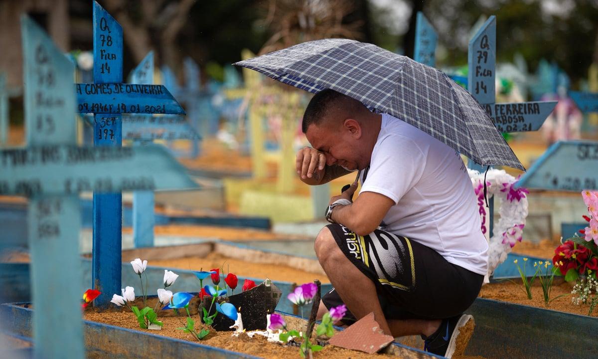 Homem chora no cemitério de Nossa Senhora Aparecida, em Manaus, no Amazonas, no Dia das Mães. Foto: Michael Dantas/AFP