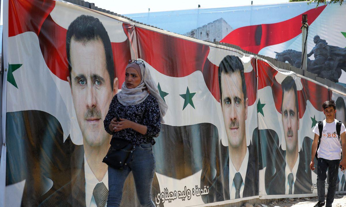 Em Damasco, capital da Síria, placas de Bashar al-Assad e dos adversários estão espalhadas pelas ruas. Foto: Louai Beshara/AFP