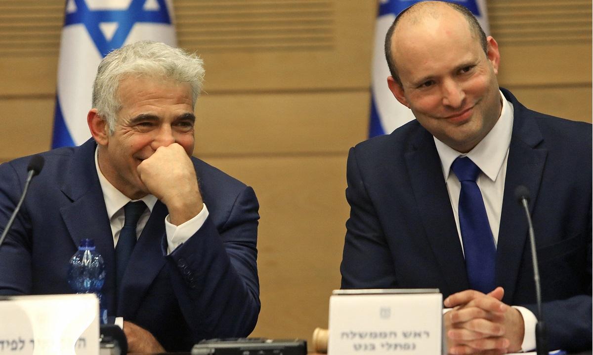 O novo primeiro-ministro de Israel, Naftali Bennett (dir.), e o primeiro-ministro suplente e ministro das Relações Exteriores Yair Lapid durante um discurso no Knesset em Jerusalém. Tudo igual? (Foto: COHEN-MAGEN / AFP)