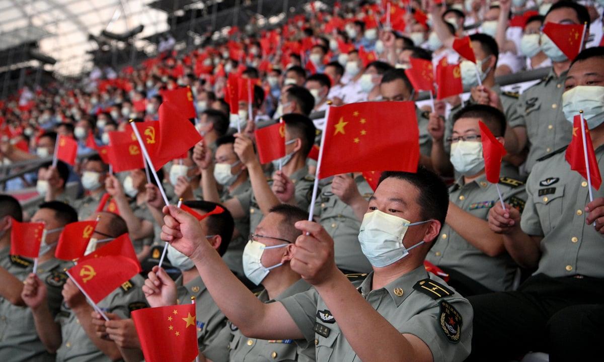 Cidadãos chineses levantam bandeiras nacionais e símbolos comunistas no aniversário centenário do partido. Foto: Noel Celis/AFP